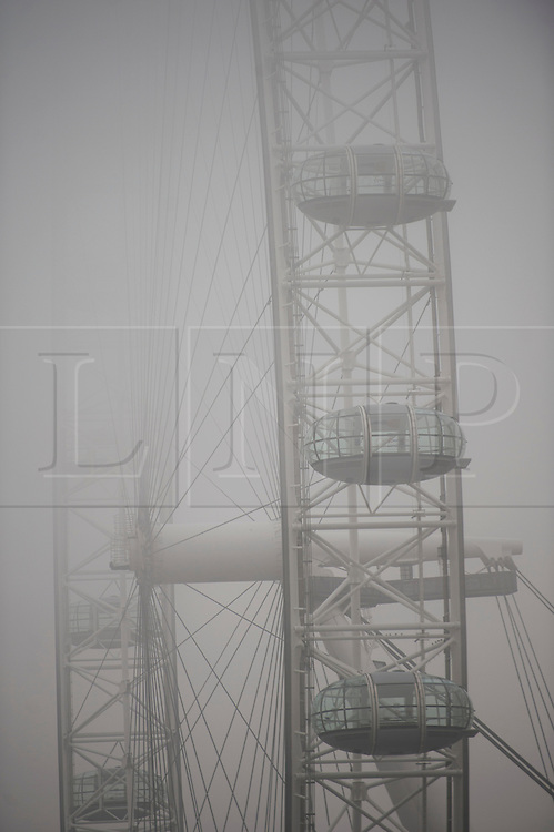 © London News Pictures. 21/01/2014. London, UK.  Pods of the London Eye disappear into fog, early morning in central London on January 21, 2014. Photo credit: Ben Cawthra/LNP