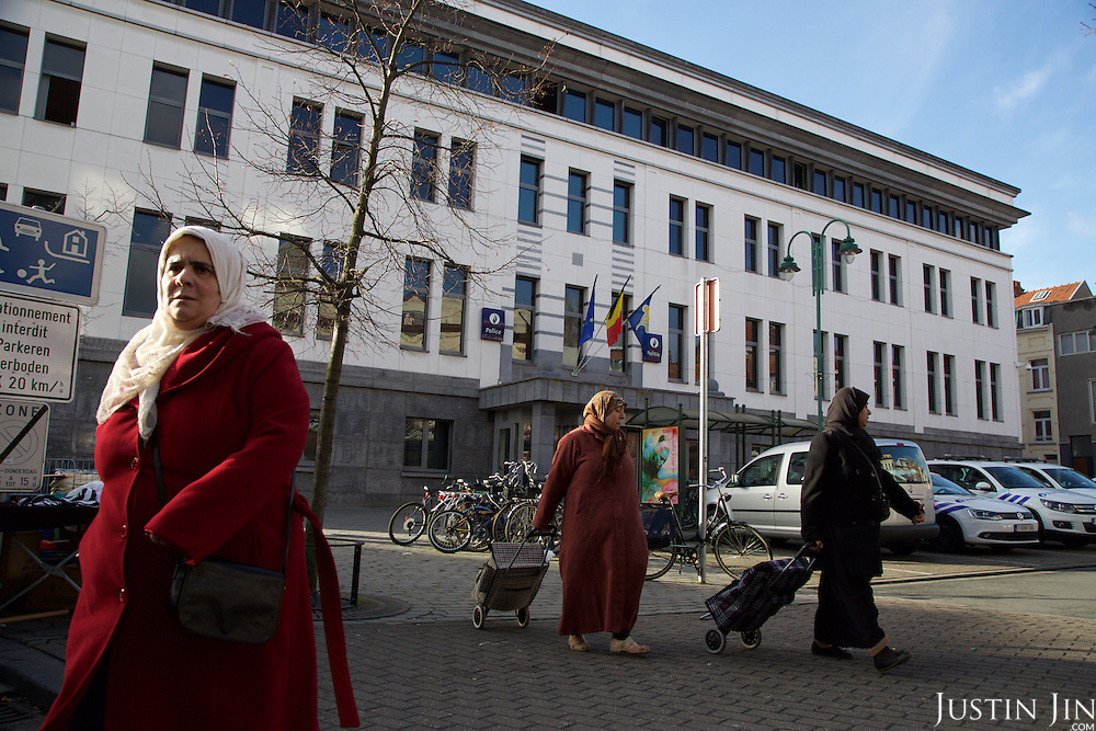 People walk in front of the central police station in Brussels' Molenbeek neighbourhood, a hotbed of Islamic fundamentalism.