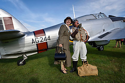 **CAPTION CORRECTION. Picture originally sent with wrong date. Picture was taken TODAY 11/09/2015** © licensed to London News Pictures. 11/09/2015<br /> Goodwood Revival Weekend, Goodwood, West Sussex. UK.<br /> The Goodwood Revival is the world's largest historic motor racing event. Competitors and enthusiasts dress in period fashions recreating the glorious days of the race circuit.<br /> Pictured. Mr & Mrs Coffey from Waterlooville, Hants, dressed in period costume pose in front of a 1942 Hawker Hunter.<br /> <br /> Photo credit : Ian Whittaker/LNP