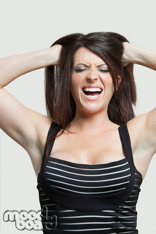 Frustrated young woman with hands in hair over gray background