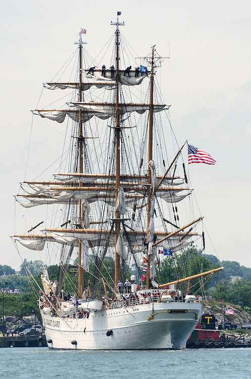 New London, Connecticut, USA - July 7, 2012: Sailors furl the sails on the US Coast Guard Cutter Eagle when it arrives at Fort Trumbull, New London, Connecticut at the conclusion of the Parade of Sail during OpSail 2012. The Eagle is a 295-foot barque used as a training ship for the United States Coast Guard.