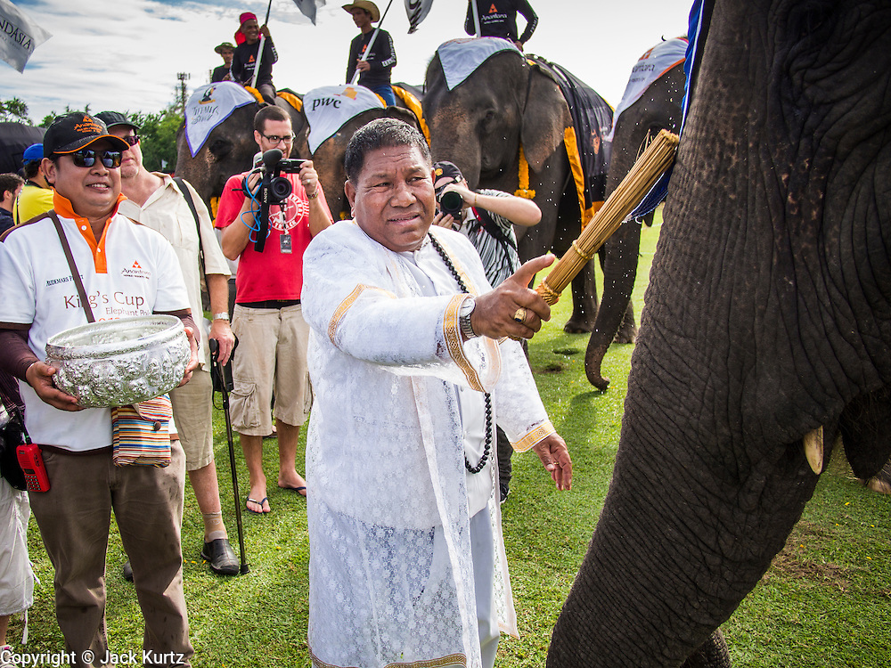 """29 AUGUST 2013 - HUA HIN, PRACHUAP KHIRI KHAN, THAILAND: A Brahmin priest blesses the elephants before the King's Cup Elephant Polo Tournament in Hua Hin. The tournament's primary sponsor in Anantara Resorts and the tournament is hosted by Anantara Hua Hin. This is the 12th year for the King's Cup Elephant Polo Tournament. The sport of elephant polo started in Nepal in 1982. Proceeds from the King's Cup tournament goes to help rehabilitate elephants rescued from abuse. Each team has three players and three elephants. Matches take place on a pitch (field) 80 meters by 48 meters using standard polo balls. The game is divided into two 7 minute """"chukkas"""" or halves. There are 16 teams in this year's tournament, including one team of transgendered """"ladyboys.""""    PHOTO BY JACK KURTZ"""