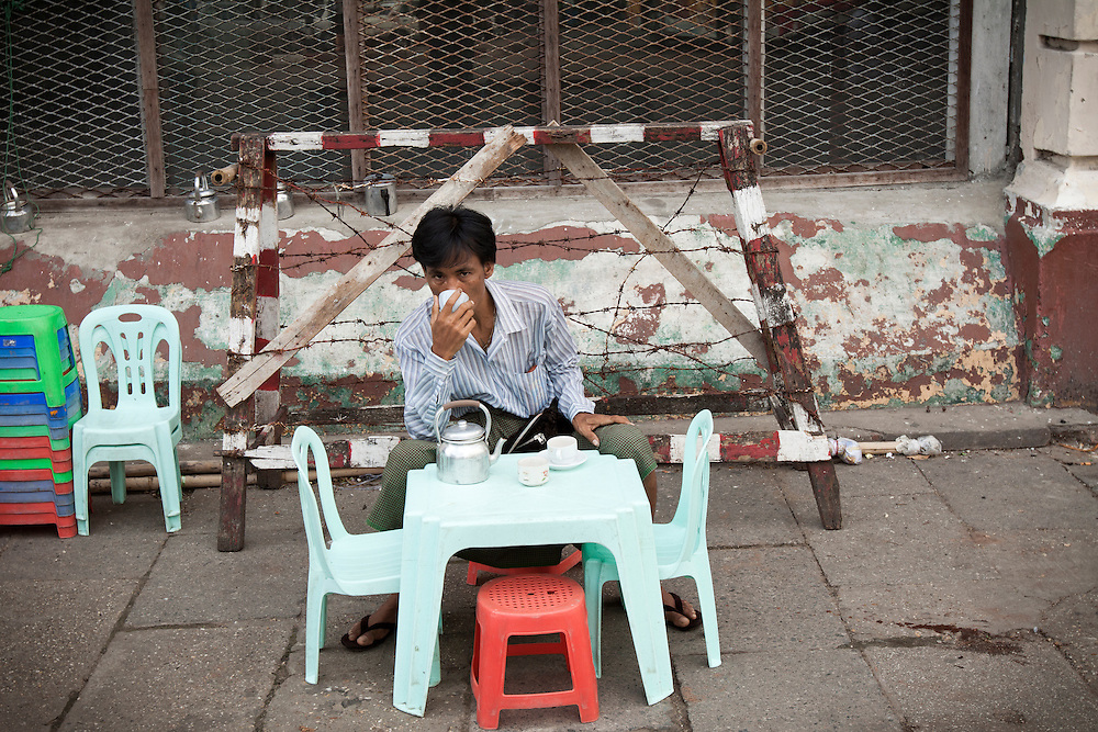 A man drinking a cup of tea in a street cafe in central Yangon in Myanmar