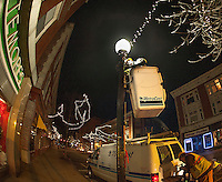 Bill DeRoy and the Metrocast crew string sets of lights giving downtown some Holiday sparkle late Wednesday evening.  (Karen Bobotas/for the Laconia Daily Sun)