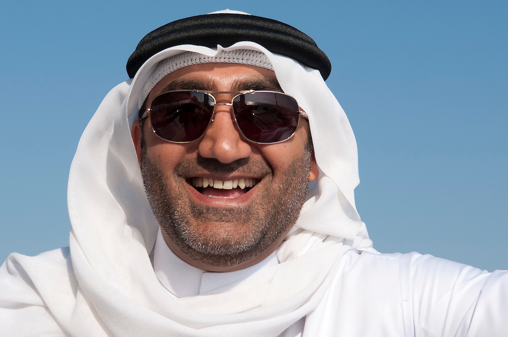 Arabian man of Dubai wearing traditional dress of dishdasha (robe) and kaffiyeh (head covering, held in place by a rope called the agal); United Arab Emirates.