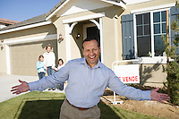Portrait of mid-adult man in front of new house