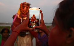 September 1, 2017 - Allahabad, Uttar Pradesh, India - Allahabad: An Indian hindu devotee take photos from her mobile during immersion of Lord Ganesha's idol in River Ganga during Ganesh Chaturthi festival celebration in Allahabad. (Credit Image: © Prabhat Kumar Verma via ZUMA Wire)