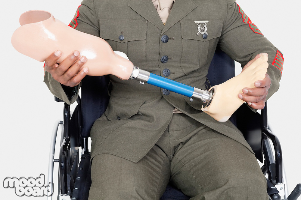 Midsection of a US military officer holding prosthesis leg as he sits in wheelchair