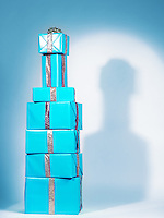 Pile of presents, stacked blue gift wrapped boxes in a shape of an alcohol bottle. Alcoholic beverage holiday concept on light blue background.
