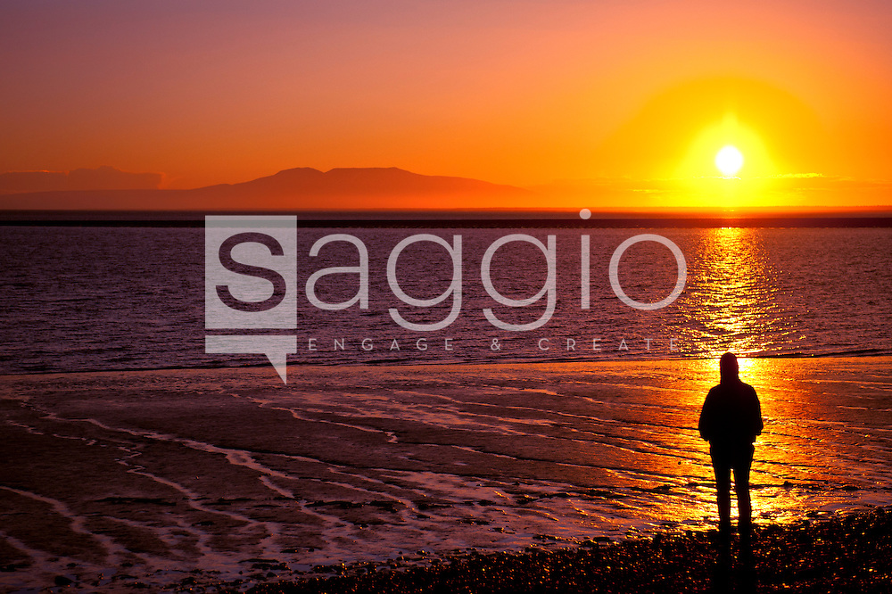 A beachcomber pauses to enjoy the summer sunset over Cook Inlet from Point Woronzof near Anchorage, Alaska.