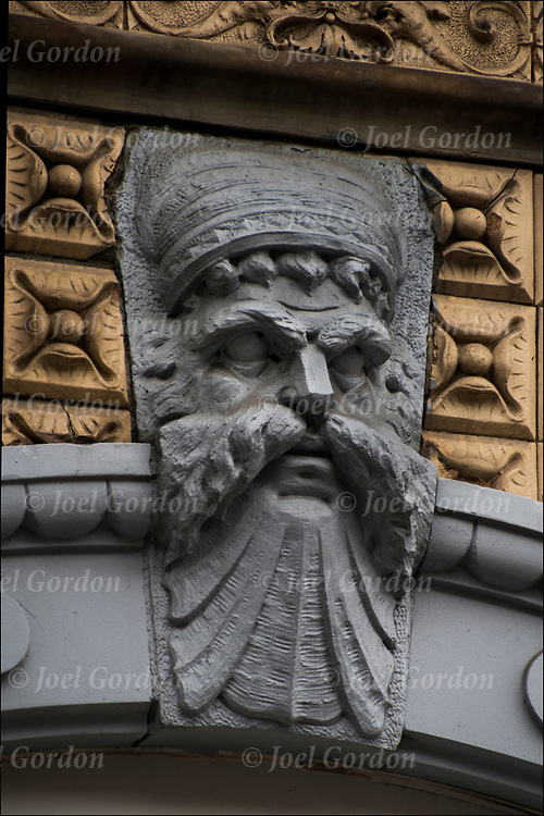 Stonework on side of 19th century building of carved face  in the East Village, NYC<br /> <br /> Around the turn of the century owners could be immortalized in stone on their own buildings.    with their proud face adorning the entrance way.