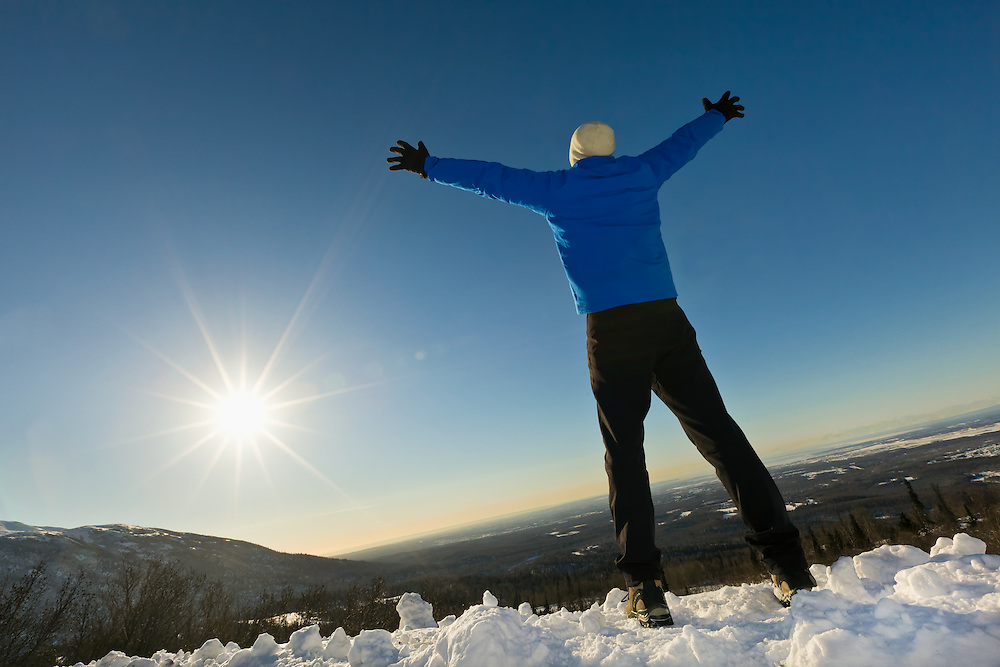A hiker holds up his arms and expresses exuberance at the late afternoon winter sun overlooking Anchorage along Arctic Valley Road in the Chugach Mountains of Chugach State Park in Southcentral Alaska. Winter. Afternoon. MR.