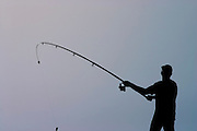 A silhouette of a fisherman in the Jaffa harbour