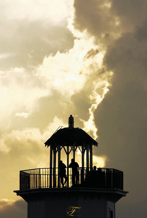 color in local- sarah merrill (L), and jacob leanna (R), of fdl watch storm clouds cover the sun during sunset from the top of the lighthouse at lakeside park wednesday. - patrick flood photo