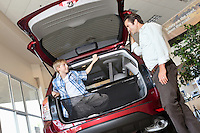 Father looking at son sitting in car trunk in showroom