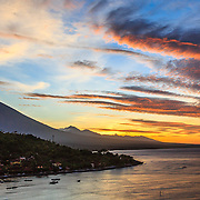 INDONESIA. Amed, Bali. July 17th, 2013. A vibrant sunset of pinks, oranges and yellows over Mount Agung, captured from Amed's lookout point.