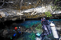 scuba divers in the entrance of dos ojos cenote in yucatan