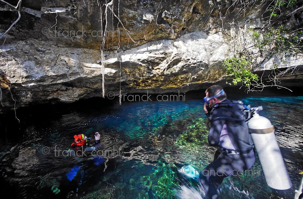 scuba divers in the entrance of dos ojos cenote in yucatan