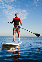A portrait of an athletic man om a paddle board on Elliott Bay / Puget Sound in the early morning.
