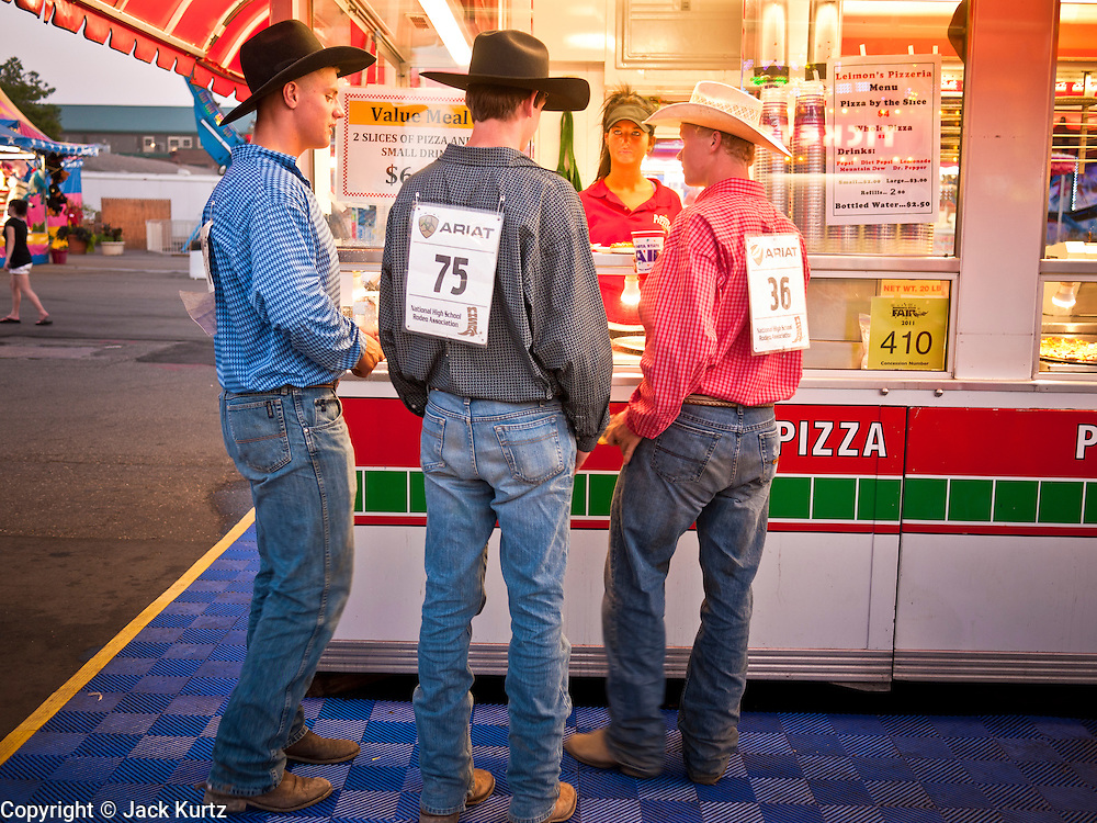 """01 SEPTEMBER 2011 - ST. PAUL, MN:  High School rodeo participants buy food at a booth on the midway at the Minnesota State Fair. The Minnesota State Fair is one of the largest state fairs in the United States. It's called """"the Great Minnesota Get Together"""" and includes numerous agricultural exhibits, a vast midway with rides and games, horse shows and rodeos. Nearly two million people a year visit the fair, which is located in St. Paul.   PHOTO BY JACK KURTZ"""