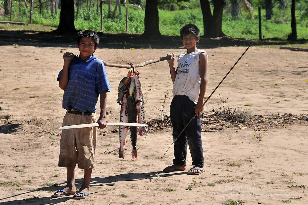 Yuracare boys bowfishing, bring home a string of fish in Villa Hermosa, Beni, Bolivia