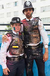 "London, August 24th 2014. Police officers maintain their good humour despite being covered in paint as thousands of Londoners of all races and cultures attend Notting Hill Carnival's ""Family friendly"" day ahead of the main carnival on August Bank Holiday Monday."