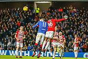 Lennard Sowah of Hamilton Academical FC gets the jump on Kyle Lafferty of Rangers to header clear during the Ladbrokes Scottish Premiership match between Rangers and Hamilton Academical FC at Ibrox, Glasgow, Scotland on 16 December 2018.