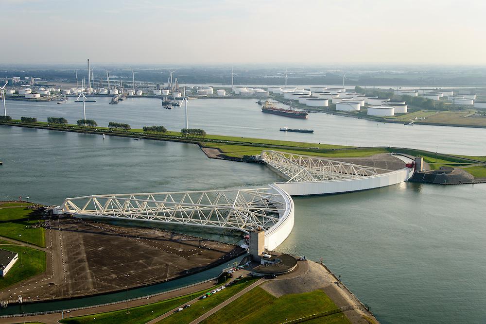Nederland, Zuid-Holland, Nieuwe Waterweg, 28-09-2014; Functioneringssluiting Maeslantkering. De waterkering in de Nieuwe Waterweg wordt eenmaal per jaar, voordat het stormseizoen begint, getest. Tijdens het sluiten van de kering ligt alle scheepvaartverkeer naar de Rotterdamse haven stil. <br /> De Maeslantkering sluit normaal gesproken alleen bij dreigende stromvloed en bij een waterstand van 3 meter of meer boven NAP. De kering, onderdeel van de Deltawerken, vormt samen met de Hartelkering de Europoortkering en beschermt Rotterdam en achterland bij extreme waterstanden. <br /> Hoek van Holland - Port of Rotterdam. Aerial view of the new storm surge barrier (Maeslantkering) in the Nieuwe waterweg during the so-called functioning closure, taking place one a year before the storm season begins. The waterway, leading to the Port of Rotterdam (at the horizon), is closed during the test.<br /> luchtfoto (toeslag op standard tarieven);<br /> aerial photo (additional fee required);<br /> copyright foto/photo Siebe Swart