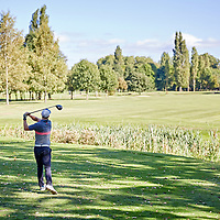 A photograph of a golfer driving off the tee stood in dappled light on a sunny day in England