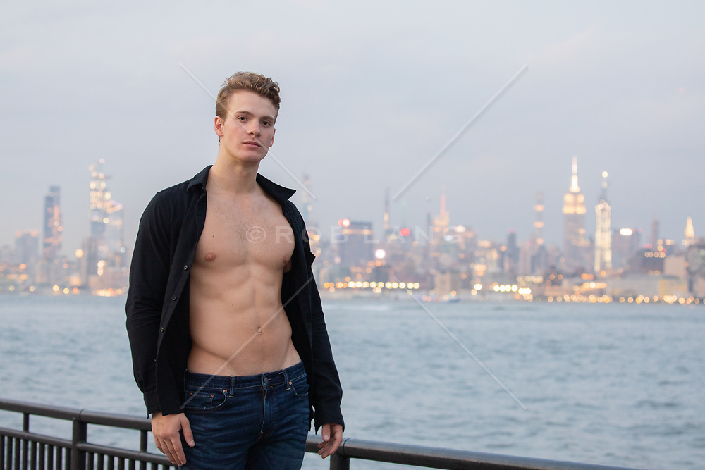hot guy with open shirt by the New York City Skyline at dusk