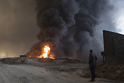 October 21, 2016 - Qayyarah, Iraqi-Kurdistan, Iraq - An Iraqi man observes plumes of thick smoke billowing from several oil wells on the edge of the neighbourhood where he lives in Qayyarah, Iraq. The wells, part of a large oilfield around the town, were set alight by retreating Islamic State militants in July 2016, but have yet to be extinguished. ..Since being retaken from the Islamic State the town of Qayyarah has become an important staging post for the Iraqi Army, and some US support elements, in the buildup to the Mosul offensive. (Credit Image: © Matt Cetti-Roberts/London News Pictures via ZUMA Wire)
