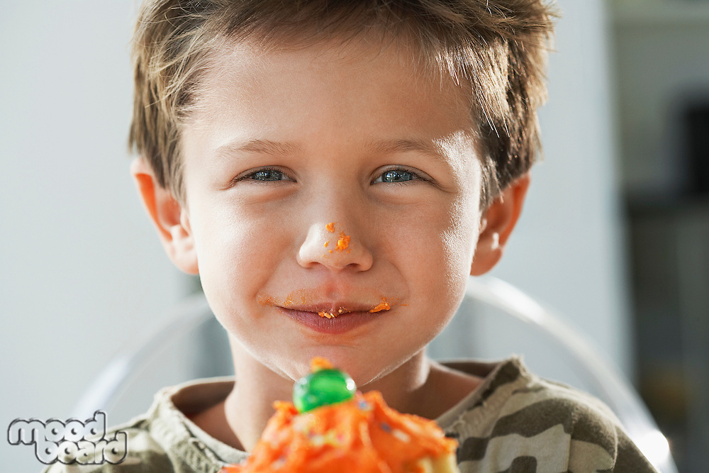 Young boy eating cupcake head and shoulders