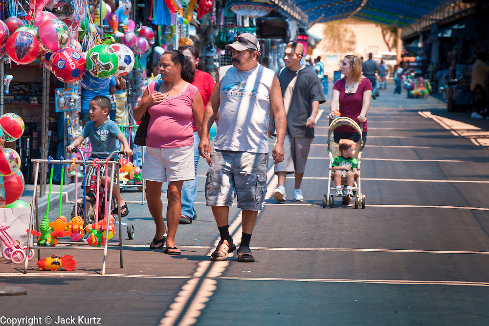July 25 - PHOENIX, AZ: People walk among the stalls at El Gran Mercado. El Gran Mercado (The Big Market) in Phoenix is the largest flea market in the Phoenix area and has served the area's immigrant community for more than 20 years. With more than 150 small independent stalls selling Mexican clothes, cowboy hats, Mariachi music and food stalls selling Mexican favorites like birria chivo (goat stew) and menudo (tripe) it was more like a Mexican market than an American mall. Business in the mercado is down more than half this year because many immigrant families, legal and illegal, are leaving Arizona before the state's tough new anti-immigrant law, SB 1070 goes into effect on July 29. SB 1070 allows local police officers to check the immigration status of people they have probable cause to believe may be in the US illegally and requires immigrants to carry their immigration papers with them at all times.    Photo by Jack Kurtz