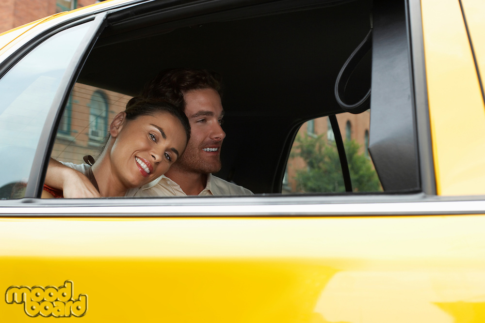 Smiling young couple in yellow taxi on urban street
