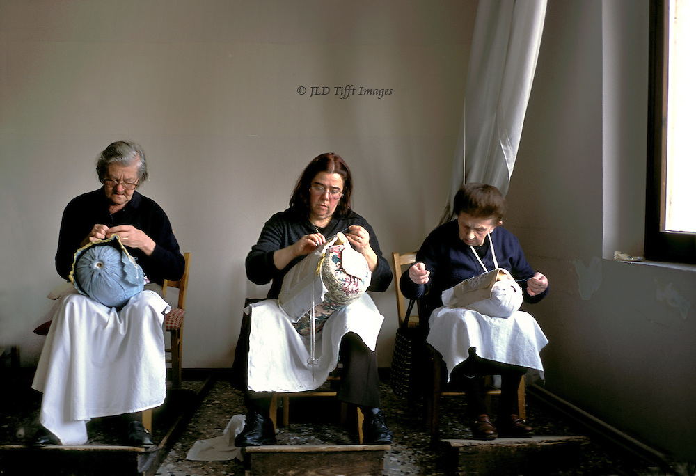 Three needlewomen seated at work in the Scuola dei Merletti on the island of Burano, Venice, Italy.  Three pairs of hands in different positions over the pillow forms on which they make their lace.  They are seated in a plain room by a window casting soft daylight.  Their feet rest on slanted boards.