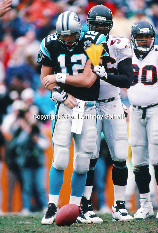 Carolina Panthers quarterback Kerry Collins (12) is grabbed by Atlanta Falcons linebacker Ron George (50) as a yellow penalty flag flies during the NFL football game against the Atlanta Falcons on Dec. 17, 1995 in Charlotte, N.C. The Panthers won the game 21-17. (©Paul Anthony Spinelli)