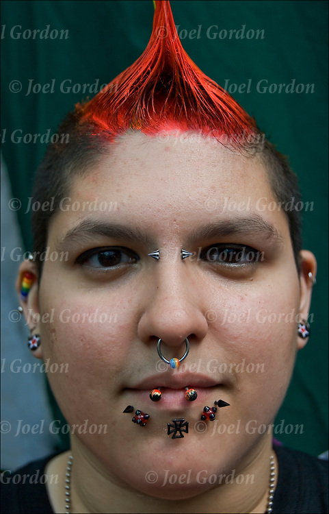 Portrait of punk &quot; Super Dyke&quot; and her many facial piercings.<br /> <br /> Facial and body piercing rings are becoming more main stream.  In some cultures this is viewed as body art. It can also be viewed as forms of anti-conformist.