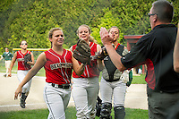 Cassie Contigiani,  Shannon Davies and Chay Cadarette give Belmont's coach Bill Cleary a high five as they head to the dugout during Friday afternoon softball with Raymond.  (Karen Bobotas/for the Laconia Daily Sun)