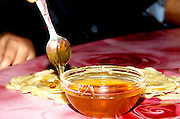 Spreading honey on a Mofletta a traditional North African-Jewish sweet pastry that is usually eaten during the Mimouna celebration on the day after Passover. served with a sweat spread filling such as Honey or Chocolate.