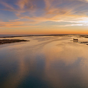 Aerial sunset panoramic and historic life-guard building at Fuseta fishing town, in Ria Formosa wetlands nature conservation park, Algarve. Portugal.