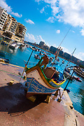 Fisherman work on his boat in Spinola Bay, in Saint Julians, Malta
