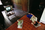 Buaphet Khuenkaew avoids working during the heat of the afternoon and dozes on the teak floor in front of the television that is showing one of her favorite Thai soap operas. Published in Material World, page 84. The Khuenkaew family lives in a wooden 728-square-foot house on stilts, surrounded by rice fields in the Ban Muang Wa village, outside the northern town of Chiang Mai, in Thailand.