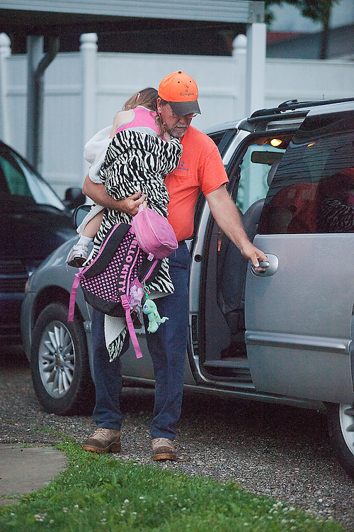 With his hands full, Dale carefully shut the car door as he brought a still sleeping Kiera to the baby sitter's house before going to work May 22. Dale, who works for the City of Huntingburg's Department of Parks and Recreation, has to leave for work before the school bus arrives.