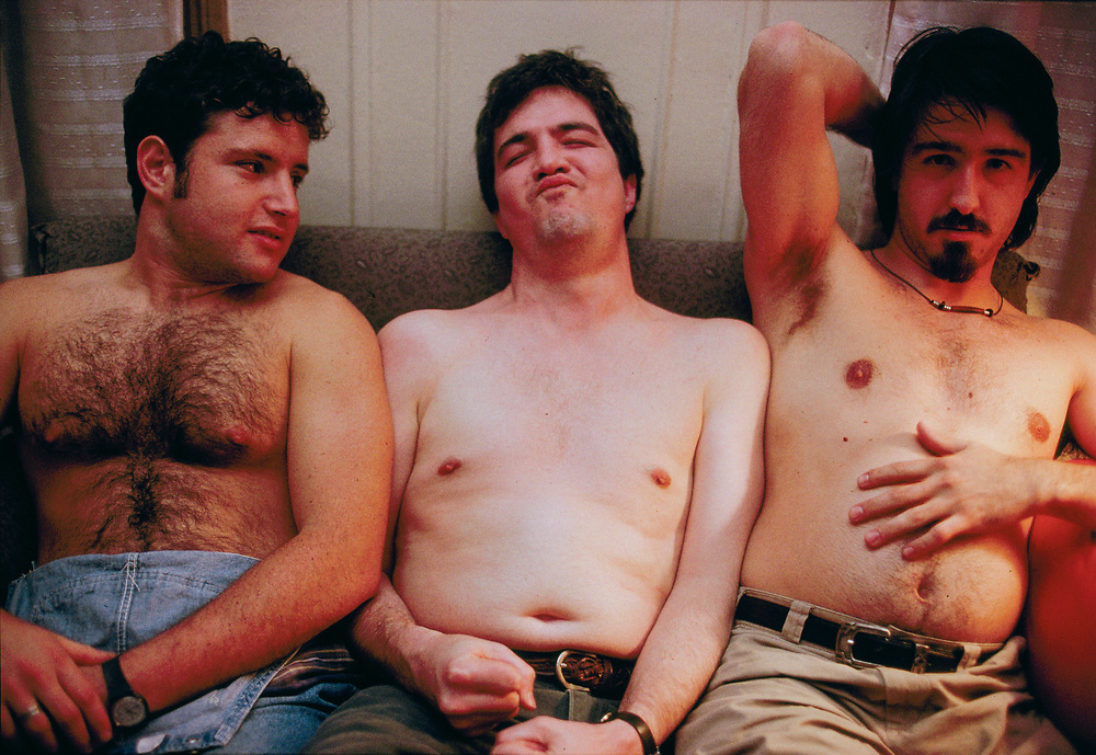 Three shirtless men sitting on a couch talking about each other's bodies