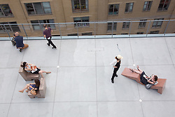 visitors to The Whitney Museum on the outdoor deck and sculpture chairs