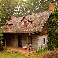 An old log cabin is nestled in the trees in the foothills of the Appalachian Mountains of North Carolina