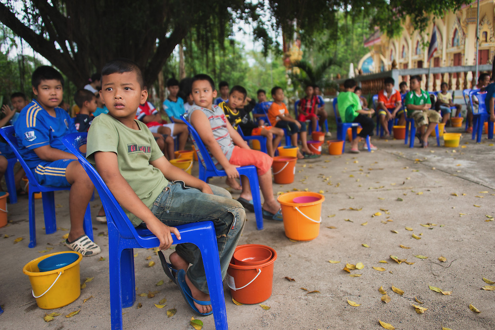 Young men wait to have their heads shaved to become novice monks in rural Nakhon Nayok, Thailand.