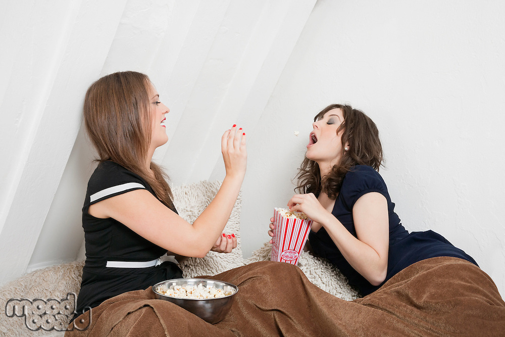 Playful young female throwing popcorn into friend's mouth in bed