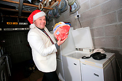 UK ENGLAND WILTSHIRE MELKSHAM 17DEC09 - Andy Park, self-proclaimed Mr Christmas shows off a large frozen turkey in his garage as he celebrates Christmas every day at his home in Melksham, Wiltshire. Mr Park, a 45-year-old divorced electrician, has consumed nearly 118,000 brussel sprouts and about 5000 bottles of Moet champagne since he decided to get into the festive spirit full-time in July 1994.jre/Photo by Jiri Rezac© Jiri Rezac 2009