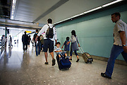 Arriving father tows young boy on wheelie suitacse after long-haul flight to Heathrow Airport's Terminal 5.